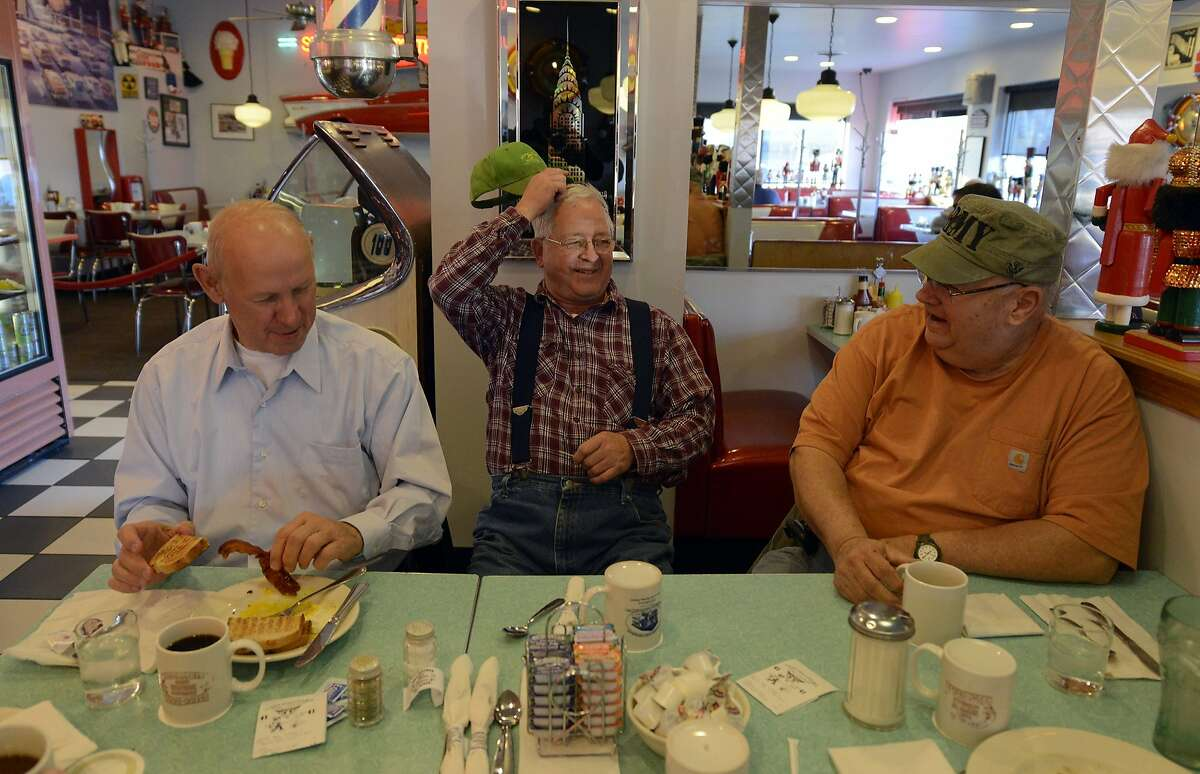 On this election day, as they do every day, people gather for breakfast in the Nutcracker Restaurant, a 1950's-style diner, in Pataskala, Ohio on Tuesday, Nov. 6, 2012. From left are Ken Armentrout, Lewie Hoskinson and Jack Cruikshank. Hoskinson, center, is a retired city worker who his friends claim is the only President Barack Obama supporter in the town of 14,000.