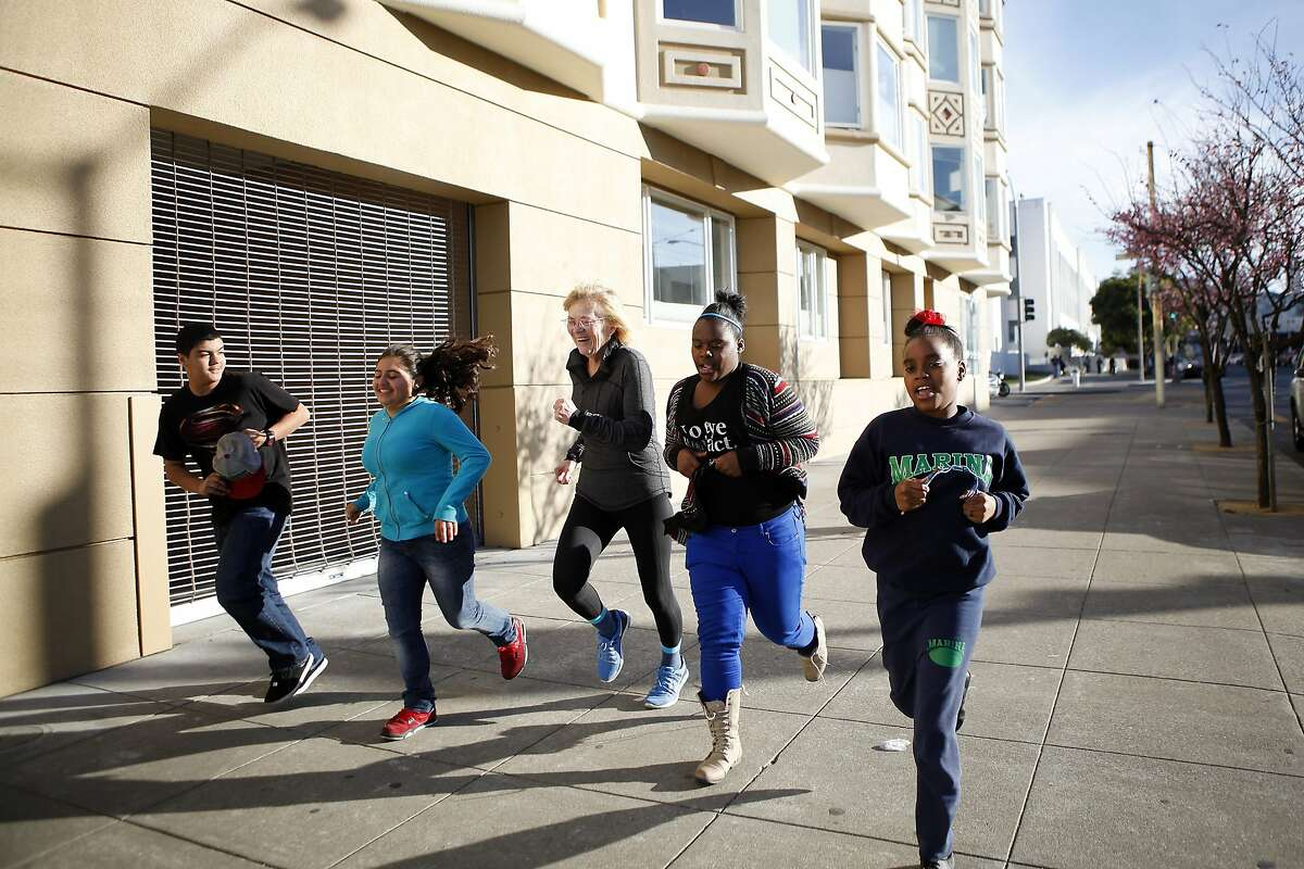 Marina Middle School Assistant Principle Ginny Daws, center, takes students (L-R) Ivan Ortega, Sofia Sanchez, Tyler Tukes and Tre'jor Barber for a run, in the Marina District of San Francisco, CA, Tuesday, January 21, 2014. In a move that has seen a decrease of suspensions, Assistant Principle Ginny Daws has started running with some students after class, an activity and approach that is part of a big shift in how the district deals with defiant kids.