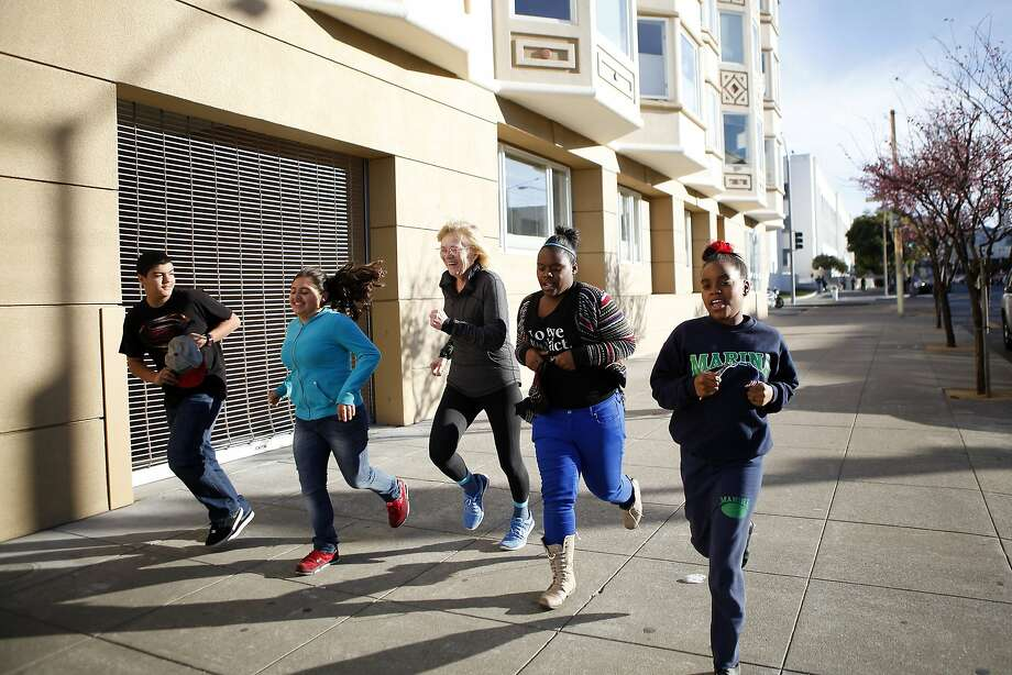 Marina Middle School Assistant Principle Ginny Daws, center, takes students (L-R) Ivan Ortega, Sofia Sanchez, Tyler Tukes and Tre'jor Barber for a run, in the Marina District of San Francisco, CA, Tuesday, January 21, 2014.   In a move that has seen a decrease of suspensions, Assistant Principle Ginny Daws has started running with some students after class, an activity and approach that is part of a big shift in how the district deals with defiant kids. Photo: Michael Short, The Chronicle