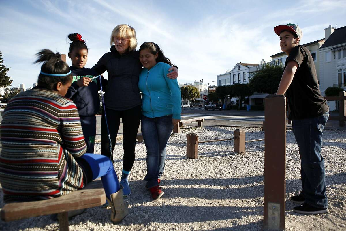 Marina Middle School Assistant Principle Ginny Daws talks with students (L-R) Tyler Tukes, Tre'jor Barber, Sofia Sanchez and Ivan Ortega as they take a break at an exercise park during their run in the Marina District of San Francisco, CA, Tuesday, January 21, 2014. In a move that has seen a decrease of suspensions, Assistant Principle Ginny Daws has started running with some students after class, an activity and approach that is part of a big shift in how the district deals with defiant kids.