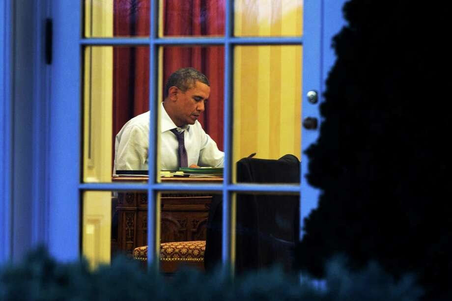 As seen from the Rose Garden, President Barack Obama works at his desk in the Oval Office of the White House in Washington, Monday, Jan. 27, 2014, ahead of Tuesday night's State of the Union speech. (AP Photo/Jacquelyn Martin) Photo: Jacquelyn Martin, STF / AP