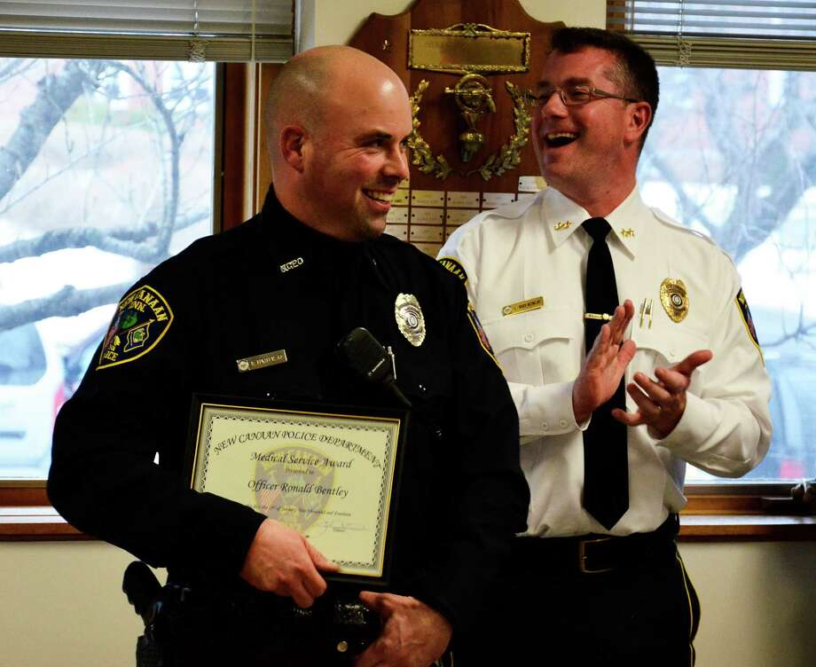 New Canaan police chief Leon Krolikowski claps for officer Robert Bentley as he receives his second Medical Service Award at the New Canaan police headquarters Monday, Jan. 27. Two weeks ago, Bentley responded to an emergency on Forest Street and ended up saving the the life of a 4-month-old baby who was not breathing. Photo: Nelson Oliveira / New Canaan News