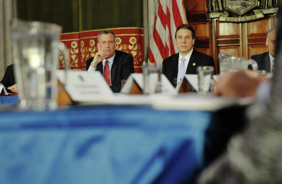 New York Mayor Bill De Blasio, left, and New York Governor Andrew Cuomo listen to a question from a member of the media during a press conference at the capitol on Monday, Jan. 27, 2014 in Albany, NY.  The Governor and the Mayor along with city legislators held the press conference to discuss the Brooklyn hospital crisis.   (Paul Buckowski / Times Union) Photo: Paul Buckowski / 00025523A
