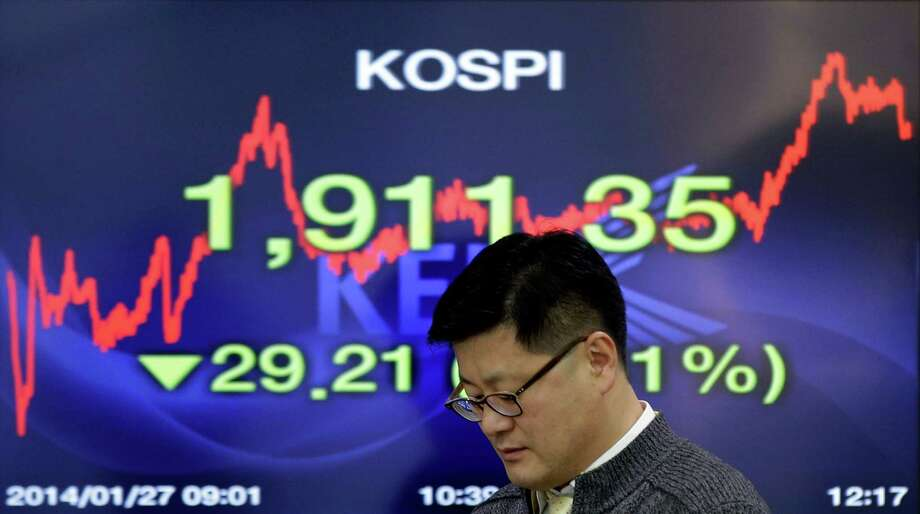 A currency trader works Monday by a screen showing the Korea Composite Stock Price Index at the Korea Exchange Bank headquarters in Seoul. Photo: Lee Jin-man, STF / AP