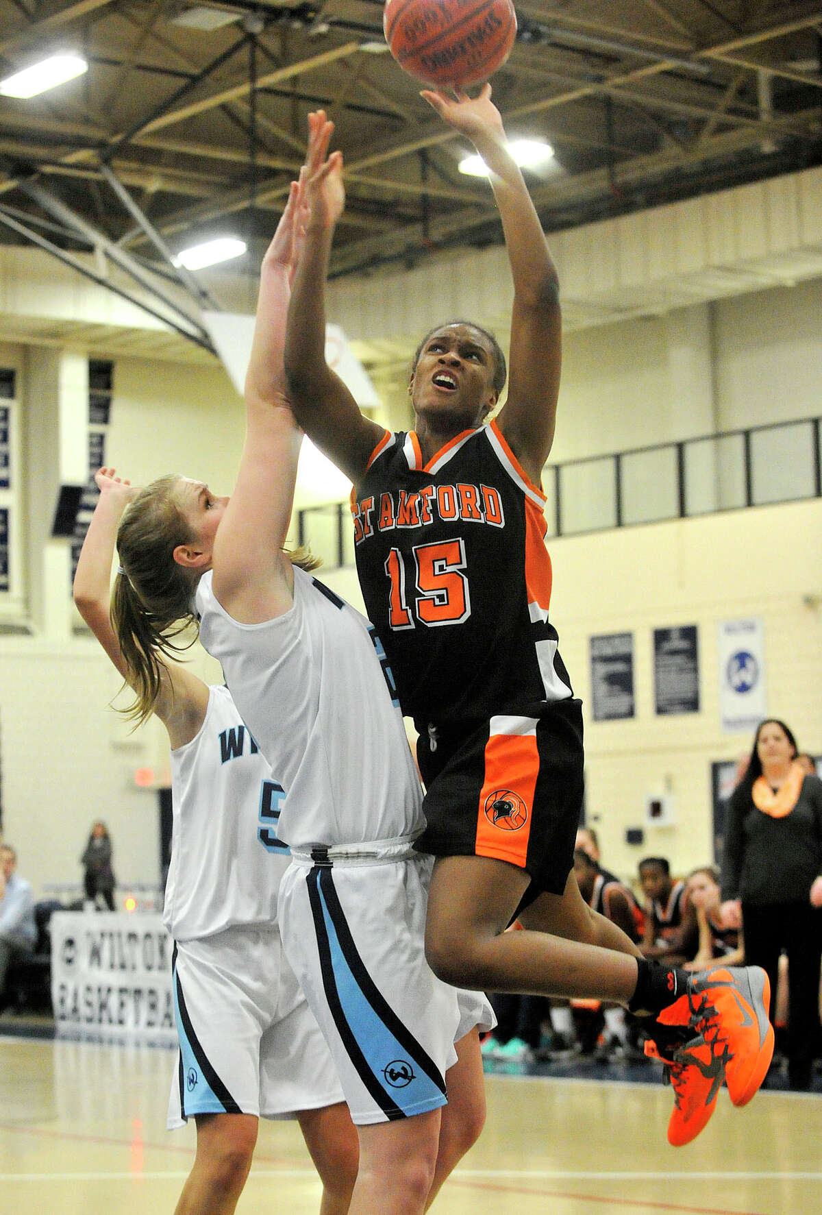 Stamford's Anisa Fortt shoots while under pressure from Wilton's Erin Cunningham during their basketball game at Wilton High School in Wilton, Conn., on Monday, Jan. 27, 2014. Stamford won, 55-50.