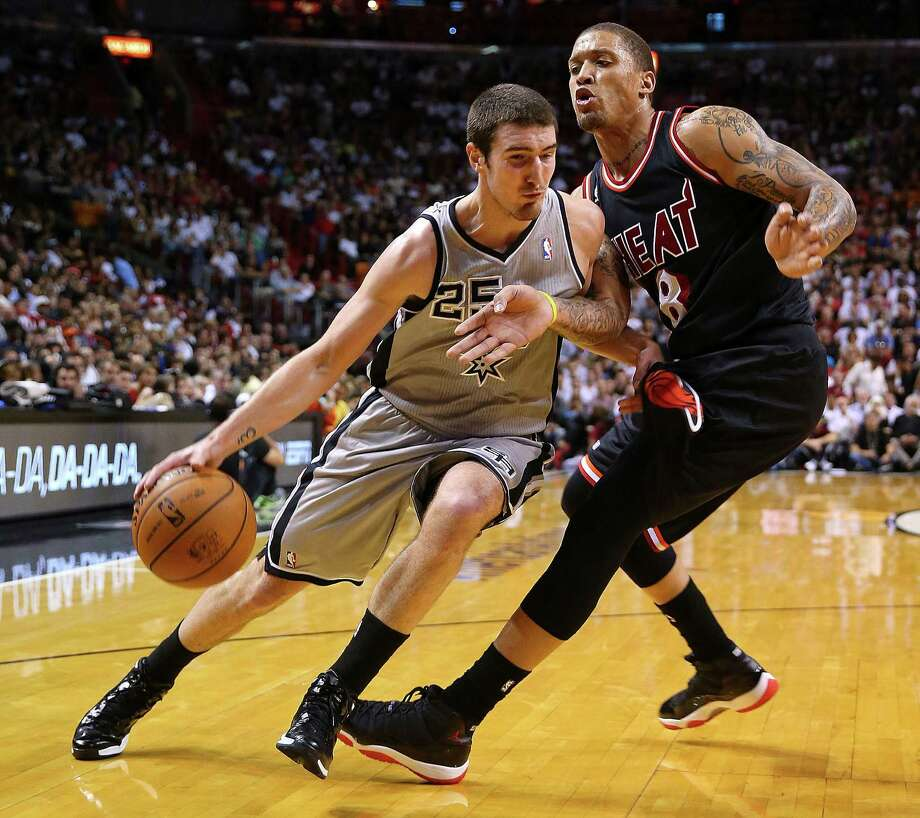 Nando De Colo (left), moving around Michael Beasley, had seven points, three assists and two rebounds against Miami. Photo: Mike Ehrmann / Getty Images / 2014 Getty Images