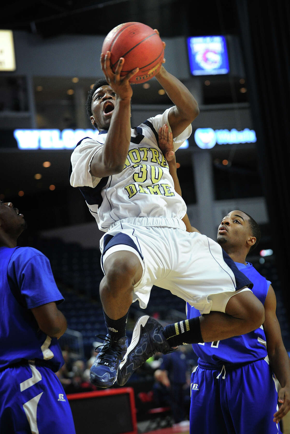 Notre Dame of Fairfield's C.J. Davidson drives to the basket between two Bunnell defenders during their boys basketball matchup at the Arena at Harbor Yard in Bridgeport, Conn. on Monday, January 27, 2014.