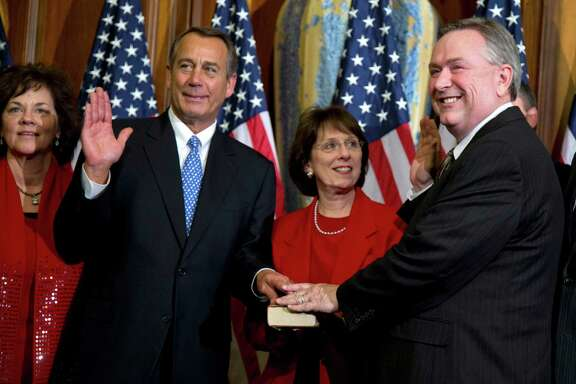 FILE - In this Jan. 3, 2013, file photo, Rep. Steve Stockman, R-Texas, right, participates in a mock swearing-in ceremony with Speaker of the House Rep. John Boehner, R-Ohio, for the 113th Congress in Washington. Stockman says he's back from a 10-day official visit to Egypt, Israel and Russia _ and is bristling at the notion he was ever missing.  (AP Photo/ Evan Vucci, File)
