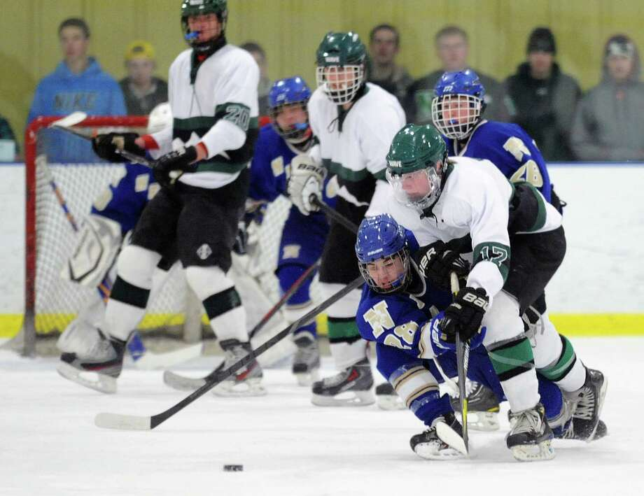 Newtown's Dominic Cartelli (28) and New Milford's Harrison O'Connell (17) battle for the puck in the high school boys hockey game between New Milford and Newtown at the Canterbury School's Drady Rink in New Milford, Conn. on Monday, Jan. 27, 2014. Photo: Tyler Sizemore / The News-Times
