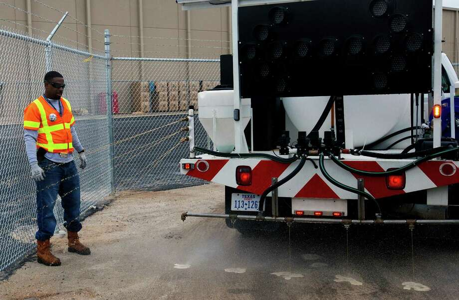 White runs a truck's de-icer distribution system on Monday in Houston. Photo: Cody Duty, Houston Chronicle / © 2014 Houston Chronicle