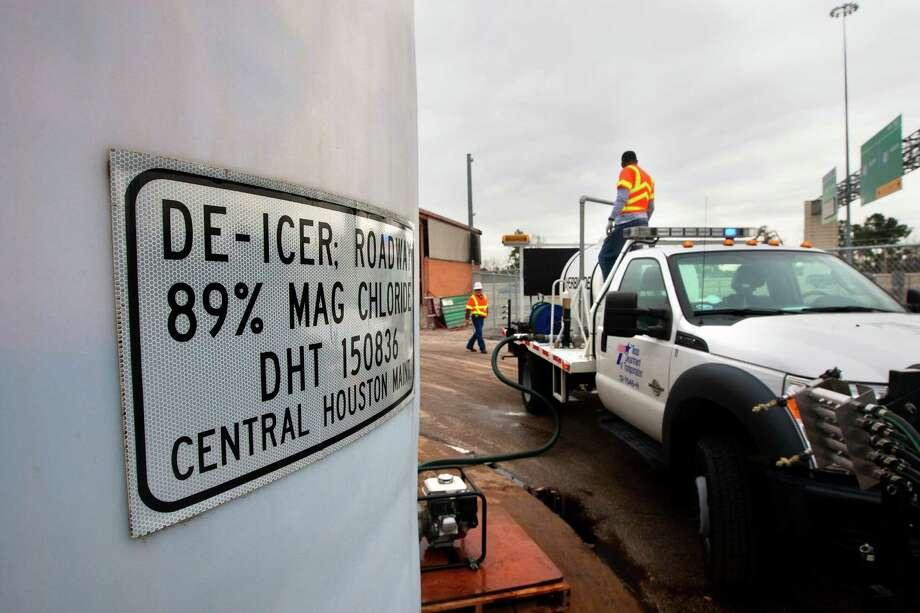 TxDOT employees Roberto Hernandez, left, and Rodgerick White fill a truck with de-icer on Monday in Houston. Crews prepped the roads for wintry conditions expected on Tuesday.  Photo: Cody Duty, Staff / © 2014 Houston Chronicle