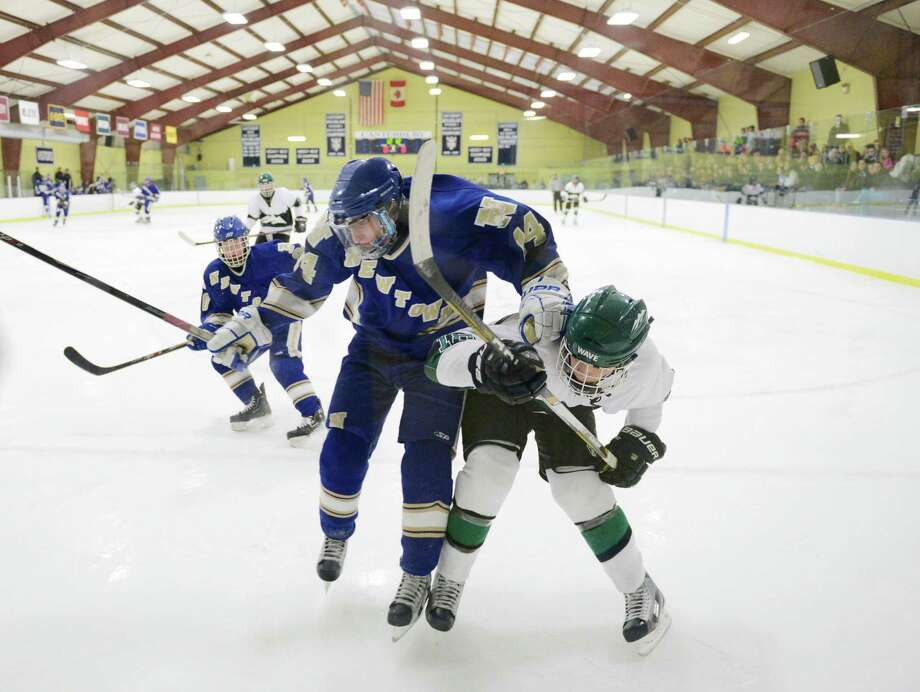 Newtown's Jonathan Lovorn (14) gets checked by New Milford's Jameson Steinhardt (18) in the high school boys hockey game between New Milford and Newtown at the Canterbury School's Drady Rink in New Milford, Conn. on Monday, Jan. 27, 2014. Photo: Tyler Sizemore / The News-Times