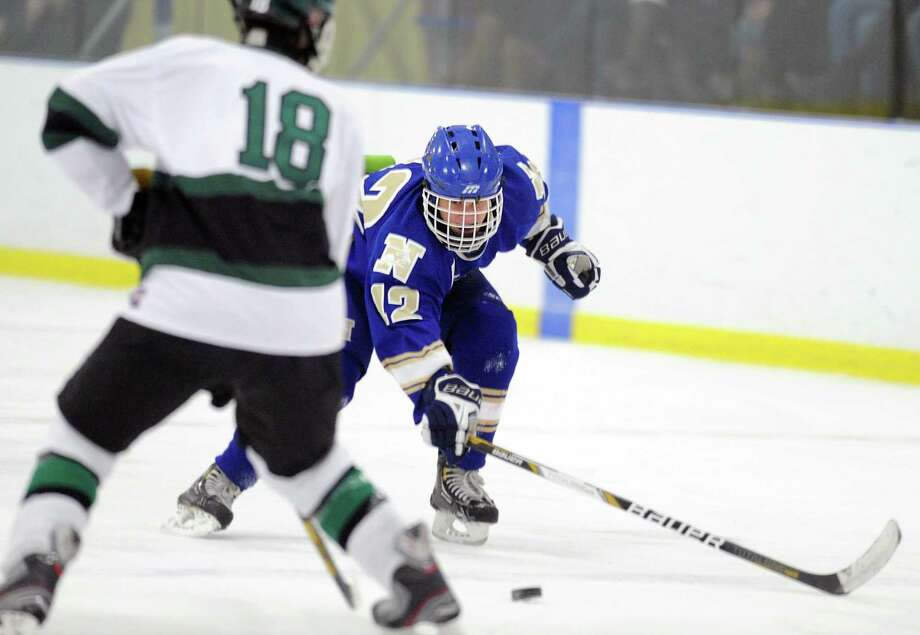 Newtown's Connor Hanley (12) reaches for the puck in the high school boys hockey game between New Milford and Newtown at the Canterbury School's Drady Rink in New Milford, Conn. on Monday, Jan. 27, 2014. Photo: Tyler Sizemore / The News-Times