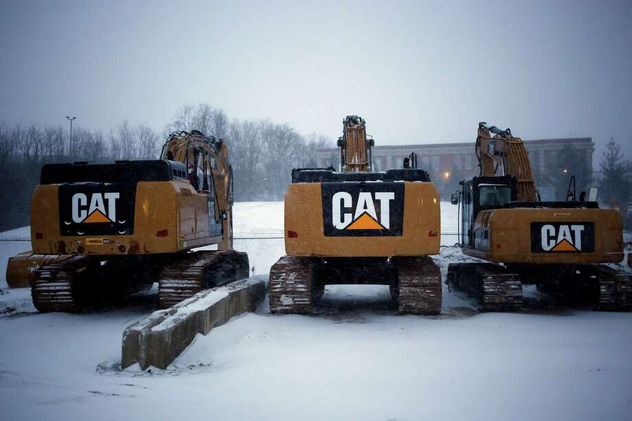 Caterpillar excavators are displayed for sale in the snow at Whayne Supply Company in Lexington, Ky. Photo: Luke Sharrett / © 2014 Bloomberg Finance LP