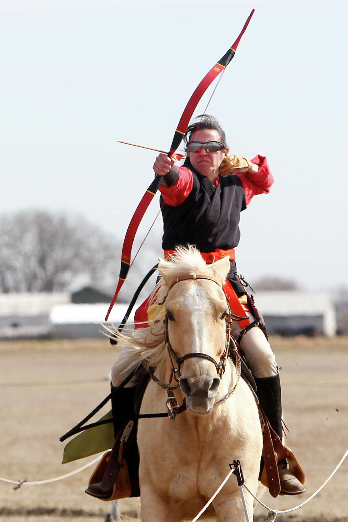 De Anne Ienna shoots at a target while atop her Palomino during a Mounted Archery Association of the Americas training session for the Bi-Continental Championship at 777 Three Mile Creek in New Braunfels on Saturday, Jan. 25, 2014. Photo by Marvin Pfeiffer / Prime Time Newspapers