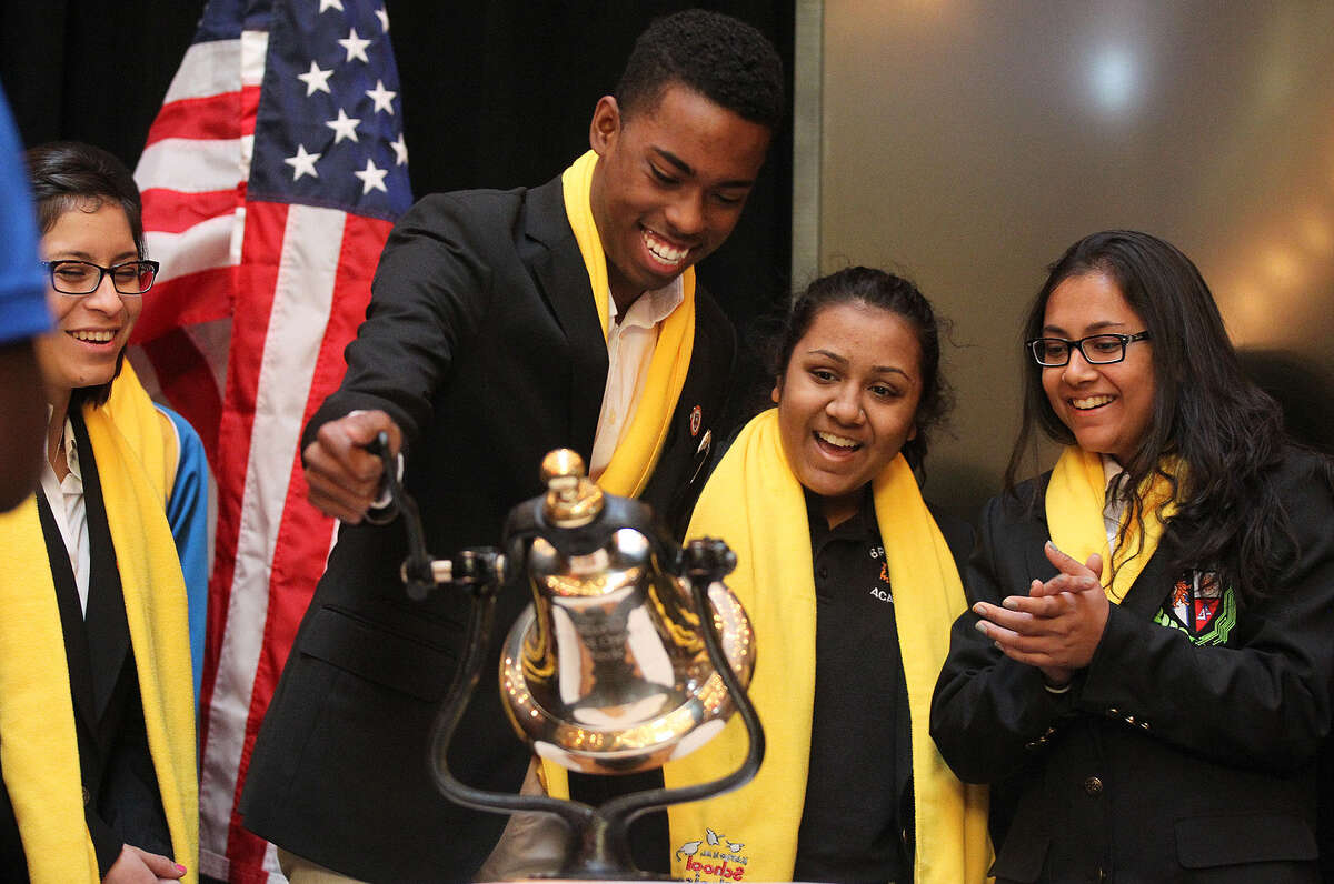 Aaron McClary, with Brooks Academy peers Julie Lopez (from left) and Mahima and Shivani Desai, rings a bell at the end.