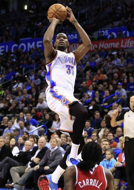 Thunder forward Kevin Durant shoots over the Hawks' DeMarre Carroll during the fourth quarter. Durant scored 41 points, including the game-winner. Photo: Alonzo Adams / Associated Press / FR159426 AP