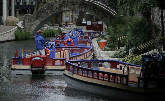 A row of empty tourist barges and a lone operator were among the sights along the River Walk as it got colder Monday. Photo: Eric Gay / Associated Press / AP
