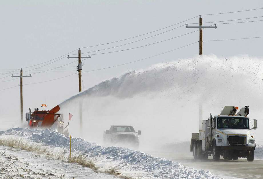 An Iowa Department of Transportation truck hurls snow over vehicles to the other side of a highway in Cedar Falls as crews battle huge snowdrifts. Photo: Matthew Putney / Associated Press / The Waterloo Courier