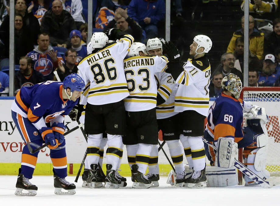 The Boston Bruins celebrate a goal by Reilly Smith while New York Islanders goalie Kevin Poulin, right, and Matt Carkner, left, react during the second period of the NHL hockey game, Monday, Jan. 27, 2014, in Uniondale, New York. (AP Photo/Seth Wenig) ORG XMIT: NYSW109 Photo: Seth Wenig / AP