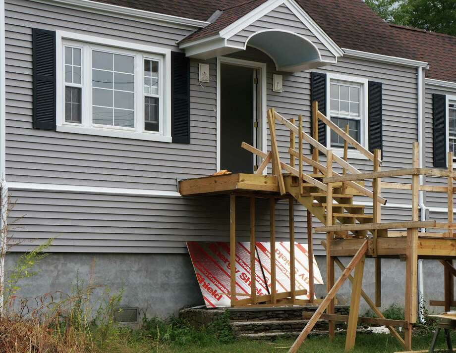 A home on Rhoda Avenue that was elevated following Superstorm Sandy. The home's original cement stairway can still be seen under the temporary wooden staircase. Photo: Genevieve Reilly / Fairfield Citizen