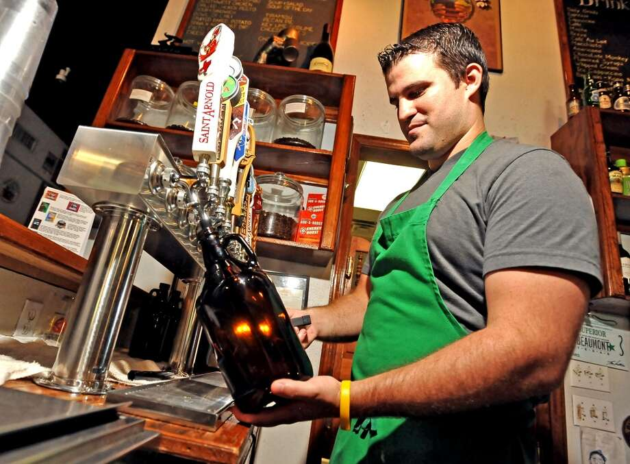 Logon Cafe bartender, Andrew Lisenby, prepares to fill a 64 ounce growler from their ten tap selection.  The growler is a great way to take home some fresh brew from a local brewery or brewpub. Photo taken Friday, September 13, 2013. Photo taken: Randy Edwards/The Enterprise Photo: Beaumont Enterprise