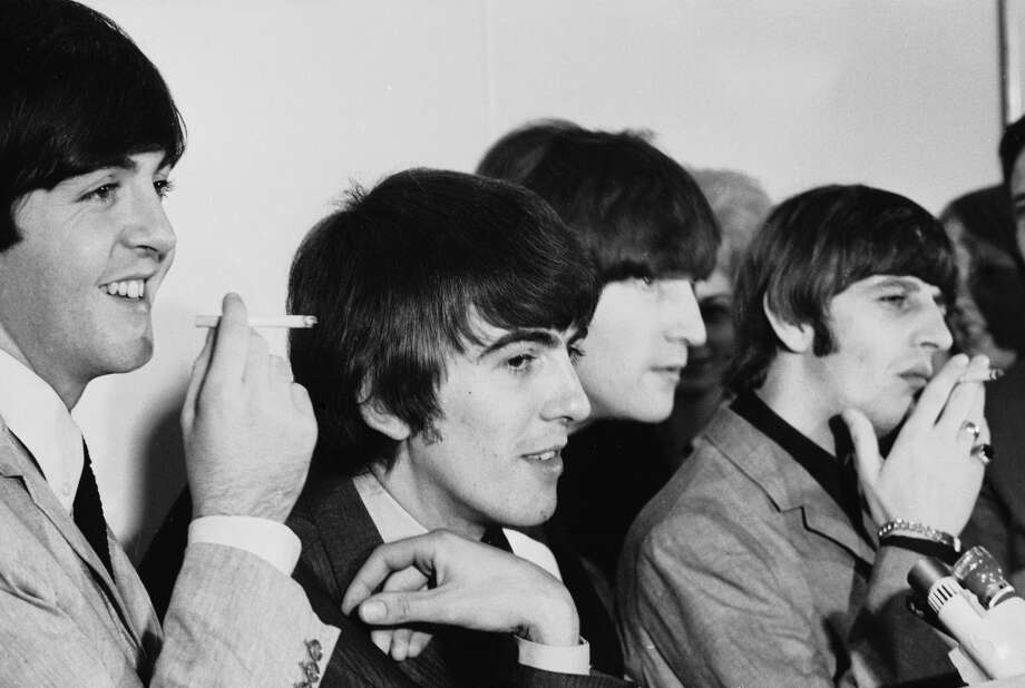 In August 1964, smoking was the epitome of rock star cool as evidenced by members of the Beatles, seen here smoking in San Francisco. (L-R) Paul McCartney, George Harrison, John Lennon and Ringo Starr, listen to questions at a press conference while McCartney and Starr smoke. (Photo by Bill Ray/Time & Life Pictures/Getty Image) Photo: Bill Ray., Time & Life Pictures/Getty Image