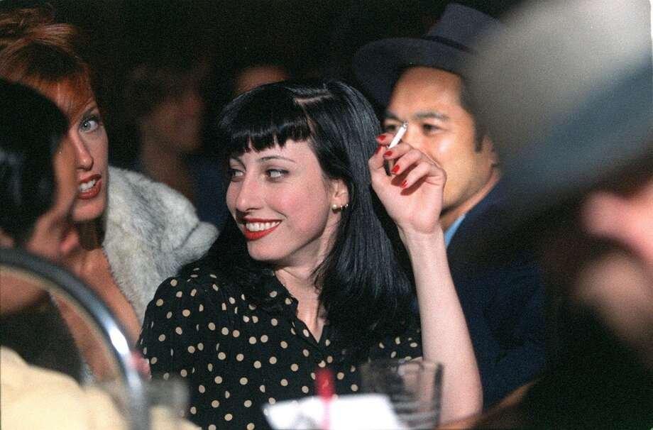 A sight that can no longer be seen in San Francisco, Cathy Walker smoking while socializing with friends at Club Deluxe. In 1998, California became the first state in the nation to require bars and gaming clubs to be smoke-free. (Photo by Liz Hafalia) Photo: LIZ HAFALIA, STAFF