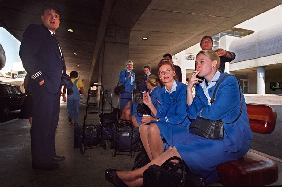 In 1996, stewardesses just arriving at San Francisco International Airport from Amsterdam smoked cigarettes while waiting for their ride. Today, smoking is permitted only in the designated smoking areas at the airport. (Photo by Liz Hafalia) Photo: LIZ HAFALIA, STAFF