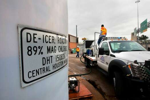 TxDOT employees Roberto Hernandez, left, and Rodgerick White fill a truck with de-icer on Monday in Houston. Crews prepped the roads for wintry conditions expected on Tuesday.  (Cody Duty / Houston Chronicle) Photo: Cody Duty, Houston Chronicle