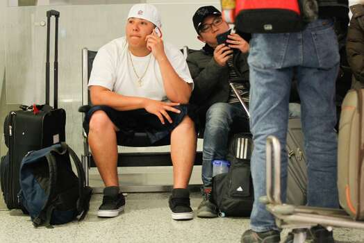 "C.J. Ochoa, 20, talks on the phone about possibly taking a bus back home to Midland at Terminal C. His flight home to Midland was canceled. Ochoa spent the last weekend on vacation in Hawaii."" this sucks it's a bummer when it happens to you and you are delayed a whole day. I need to get back home and get back to work."" (Johnny Hanson / Houston Chronicle) Photo: Johnny Hanson, Houston Chronicle"