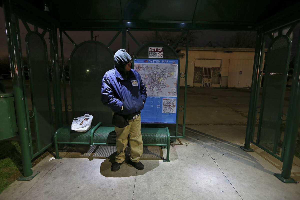 Armando Hernandez waits for the bus along Old Highway 90 on Tuesday, Jan. 28, 2014. Temperatures are in the low 30's with wind chill factors in the high 20's. Schools throughout the area remain open. Hernandez was on his way to work.