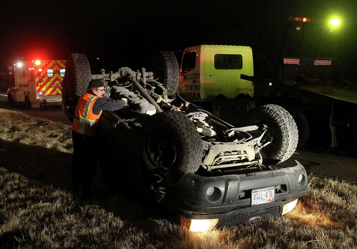 A wrecker driver prepares to upright a pickup truck that overturned Tuesday morning shortly after 6:00 a.m. during cold and slightly wet conditions on Interstate 10 eastbound near Pine and New Braunfels streets. An officer at the scene said the driver was not seriously injured. The officer also warned for motorists to be aware of de-icing vehicles on the highways.