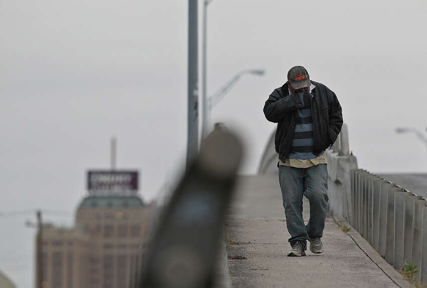 Luis Rojas covers his face as he crosses the Buena Vista Street bridge, Tuesday, Jan. 28, 2014. Temperatures are in the low 30's with wind chill factors in the 20's. Schools throughout the area remain open.