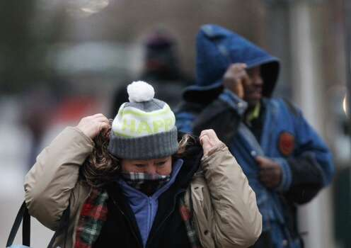 "Berta Sosa bundles up as she walk to work in downtown. ""I'm very cold and it's only going to get worse."" (Cody Duty/Houston Chronicle)"