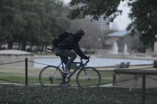 A bicyclist dressed for the cold rides through Hermann Park. (James Neilsen/Houston Chronicle)