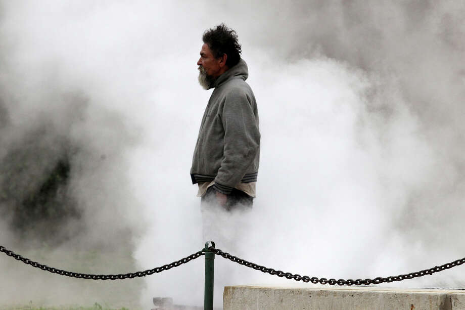 Jose Salazar stays warm by standing over a steaming grate at Bowie and East Market streets. Photo: John Davenport, San Antonio Express-News / ©San Antonio Express-News/Photo may be sold to the public