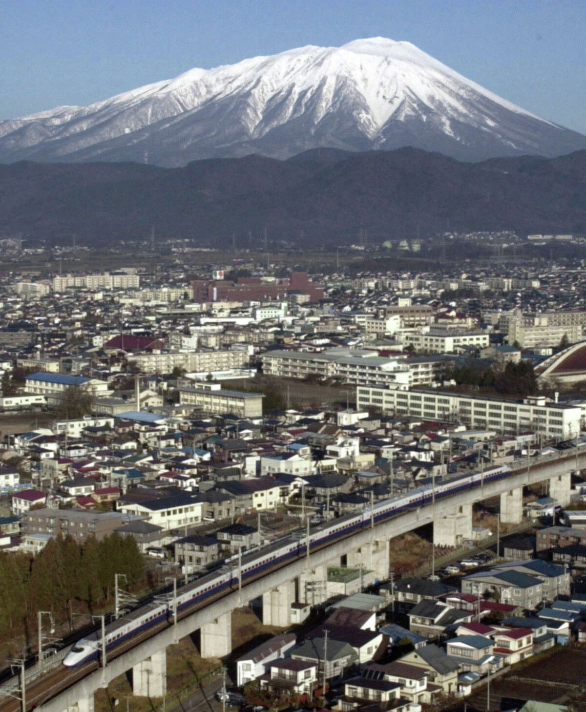 With a backdrop of the snow-capped Mount Iwate, the first train, the Hayate, of the new bullet-train service travels for Tokyo after leaving Hachinohe station in northern Japan on Dec. 1, 2002.
