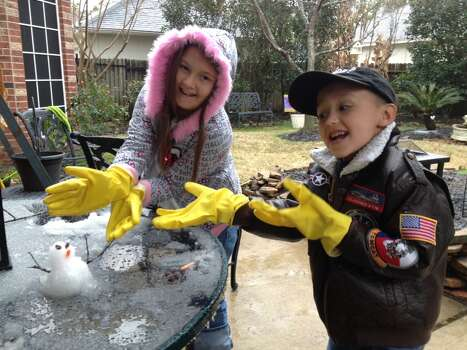 Taylor Waguespack, left, and Brent Waguespack build a tiny snowman in Atascocita on Tuesday, Jan. 28. (Deborah Waguespack)
