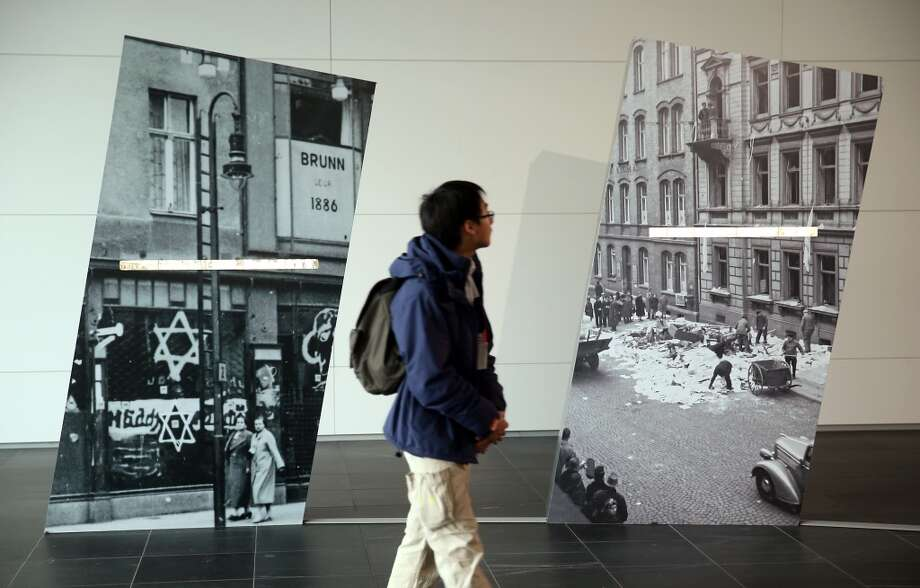A visitor walks past photographs showing the aftermath of the 1938 Kristallnacht pogroms in the German cities of Berlin (L) and Kassel at an exhibit at the Topography of Terror museum on Nov. 8, 2013 in Berlin, Germany. Events took place across Germany this weekend to commemorate the 75th anniversary of Kristallnacht, when on Nov. 10, 1938 Nazi gangs across Germany and Austria burned down over 1,000 synagogues, smashed Jewish-owned businesses, looted Jewish residences and killed several hundred Jews. Anti-Semitism was a central component of Adolf Hitler's rise to power and won him wide-spread sympathy among ordinary Germans and Austrians.  (Photo by Sean Gallup/Getty Images) Photo: Sean Gallup, Getty Images