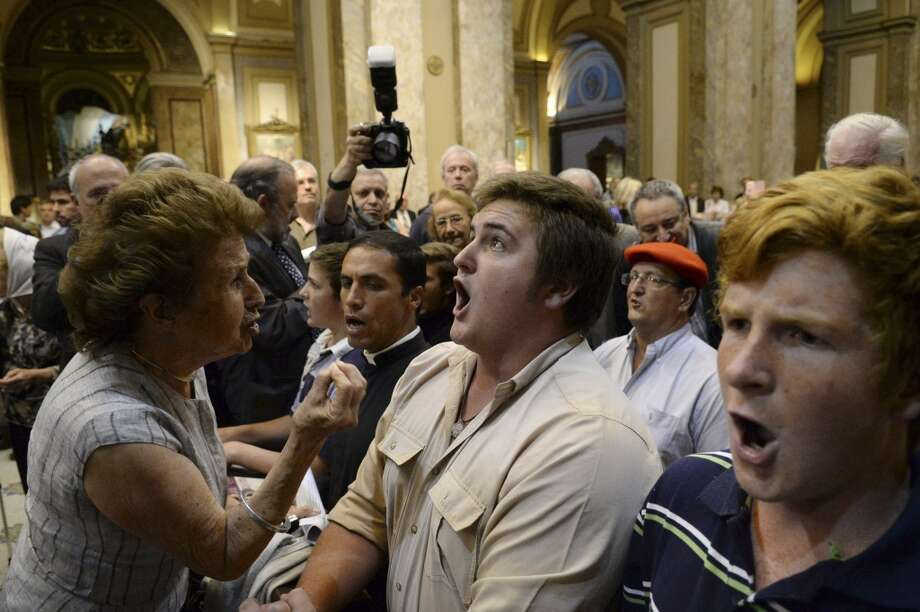 "A woman attending a ceremony that marks the beginning of the Holocaust, left, tries to stop ultra-traditionalist Catholics from interrupting an interfaith event at the Metropolitan Cathedral in Buenos Aires, Argentina, late Tuesday, Nov. 12, 2013. The small group disrupted by shouting the rosary and the ""Our Father"" prayer, and spreading pamphlets saying ""followers of false gods must be kept out of the sacred temple."" The annual ceremony brings together Catholics, Jews and Protestants to mark Kristallnacht. (AP Photo/Rodolfo Pezzoni,DyN) Photo: Rodolfo Pezzoni, Associated Press"