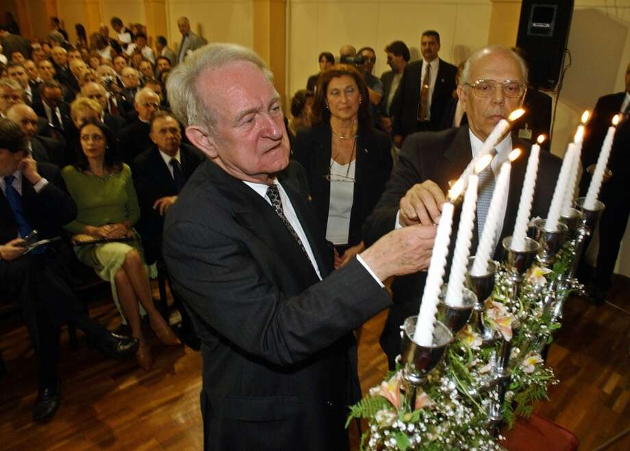 "German President Johannes Rau, left, and his counterpart Uruguayan President Jorge Batlle light candles during a commemoration ceremony in a B'nai B'rith Jewish organization center in Montevideo, Uruguay on Wednesday, Nov.  26, 2003. Rau is attending the ceremony to commemorate the November 9-10, 1938 massacres, also known as Kristallnacht or the ""Night of Broken Glass."" (AP Photo/Marcelo Hernandez) Photo: MARCELO HERNANDEZ, AP"