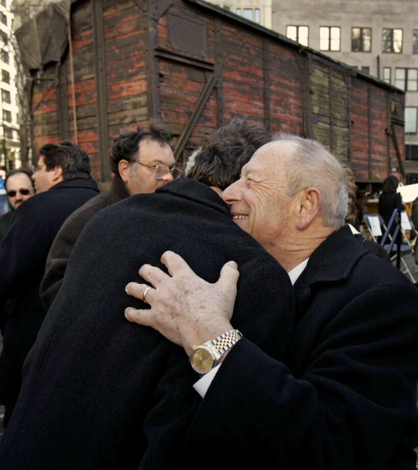 "Samuel R. Harris, right, a Holocaust survivor and president of the Holocaust and Memorial Foundation of Illinois, gets a hug from State Sen. Jeffrey Schoenberg in front of a Nazi-era German rail car Wednesday, Nov. 9, 2005, that was unveiled on the 67th anniversary of the infamous Kristallnacht, or ""Night of Broken Glass,"" in Chicago. The car will become the anchor artifact of the Museum and Education Center which is slated to open in Skokie, Ill. in 2008. The rail car is the type used by the Nazis during the Holocaust to transport Jews to concentration camps. Harris was  8-years-old when he rode in a similar ""cattle car"" in Poland in May 1942. (AP Photo/M. Spencer Green) Photo: M. SPENCER GREEN, AP"