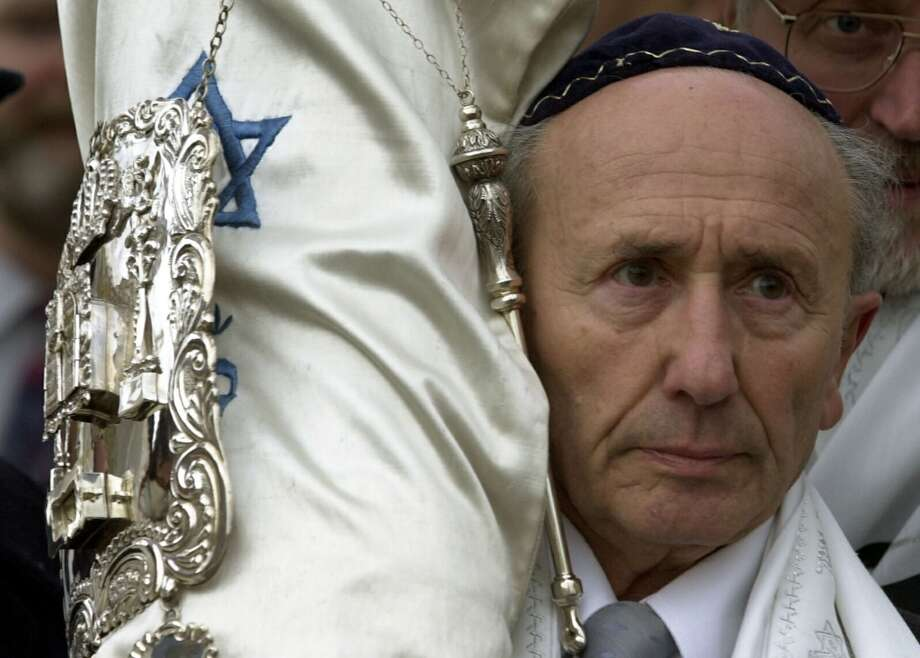 Roman Koenig, Chairman of the Jewish parish in Dresden holds a Torah roll during a procession at the inauguration ceremony for a new synagogue in Dresden, Germany, Friday, Nov. 9, 2001.  63 years after the Nazis destroyed more than 1,300 synagogues during Kristallnacht, on Nov. 9, 1938, the inauguration for the new synagogue takes place on the site where the old one stood.  (AP Photo/Matthias Rietschel) Photo: MATTHIAS RIETSCHEL, AP