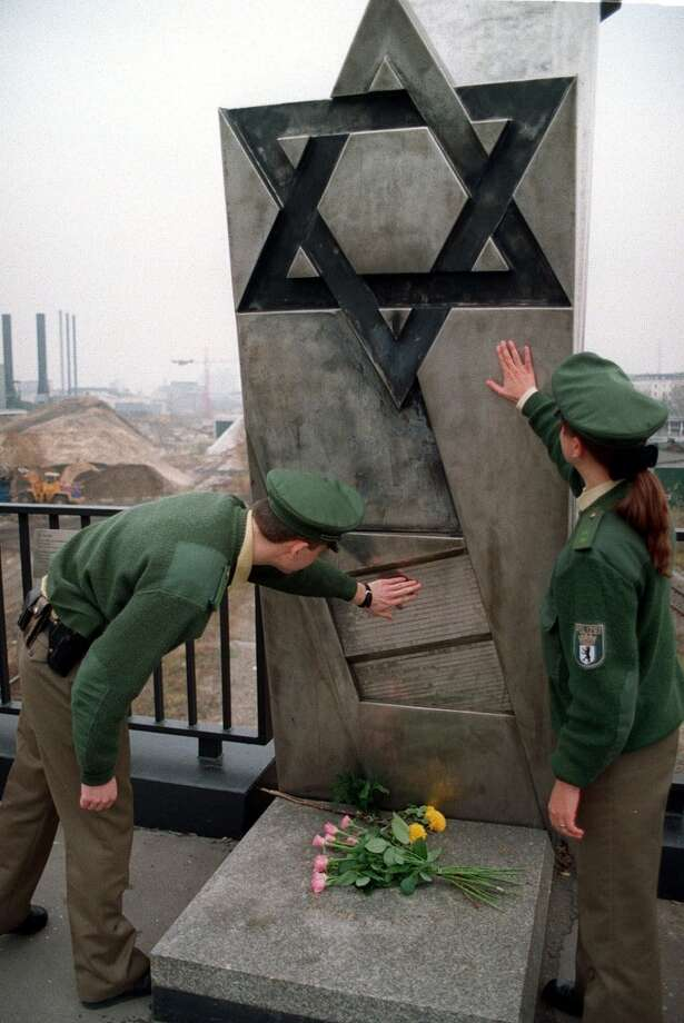 Police check a Jewish stone monument on a railway bridge in Berlin Monday, November 9,1998, on the 60th anniversary of the Kristallnacht pogrom (Night of Broken Glass) when Nazi storm troopers destroyed Jewish businesses and synagugues in Germany and Austria. Three small swastikas were scratched around a Star of David on the monument. It was not known exactly when the latest vandalism occured, police said. (AP Photo/Jan Bauer) Photo: JAN BAUER, AP