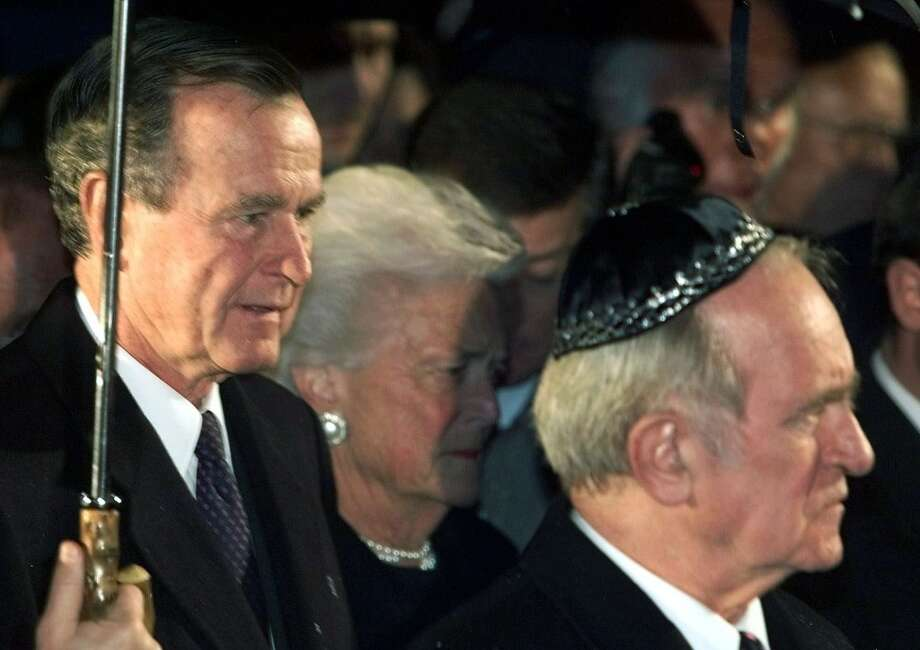 Former U.S. President George Bush, left, and his wife Barbara attend a memorial service in the Jewish community center in Berlin on November 9, 1999 commemorating the 61st anniversary of Nazi Germany's Kristallnacht, the 1938 night of orchestrated nationwide attacks on Jewish stores, synagogues and cemeteries that presaged the Holocaust. Bush is also in Berlin to celebrate the 10th anniversary of the fall of the Berlin wall which also took place on a November 9.  At right is German President Johannes Rau. (AP Photo/Herbert Knosowski) Photo: HERBERT KNOSOWSKI, AP