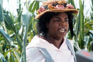 Oprah Winfrey with a hat on walking through the corn fields in a scene from the film 'The Color Purple', 1985.