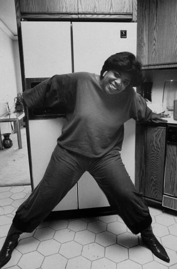 Talk show hostess-actress Oprah Winfrey bracing herself against her refrigerator, as if using willpower not to open it, 1985. Photo: Kevin Horan, Time & Life Pictures/Getty Image