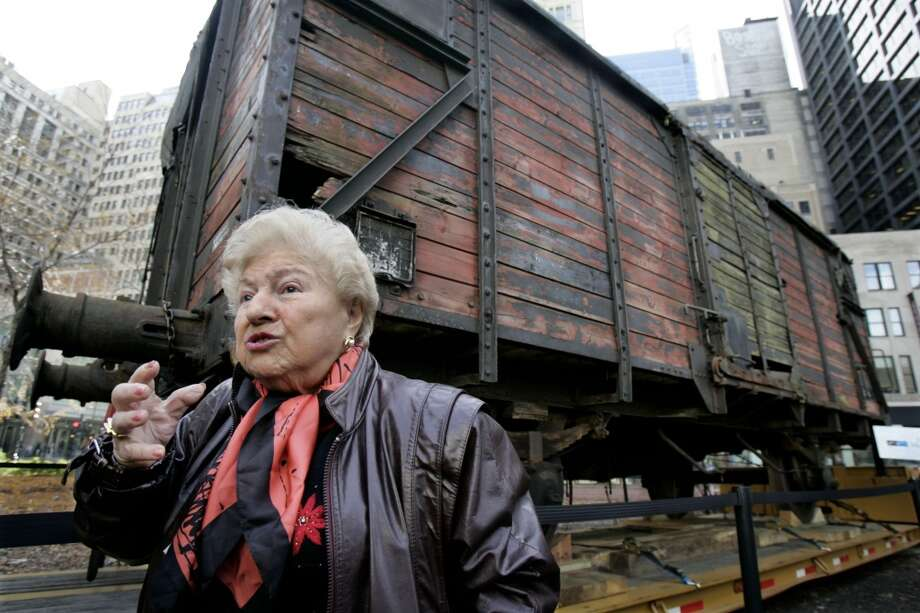 "Holocaust survivor Barbara Steiner stands in front of a Nazi-era German rail car Wednesday, Nov. 9, 2005, that will become the anchor artifact of the Illinois Holocaust Museum and Education Center which is slated to open in Skokie, Ill., in 2008. The rail car, unveiled on the 67th anniversary of the infamous Kristallnacht, or ""Night of Broken Glass,"" is the type used by the Nazis during the Holocaust to transport Jews to concentration camps. Steiner rode in such a car when she and her family were taken to the Majdanek death camp in Poland after the 1943 Warsaw ghetto uprising. (AP Photo/M. Spencer Green) Photo: M. SPENCER GREEN, AP"