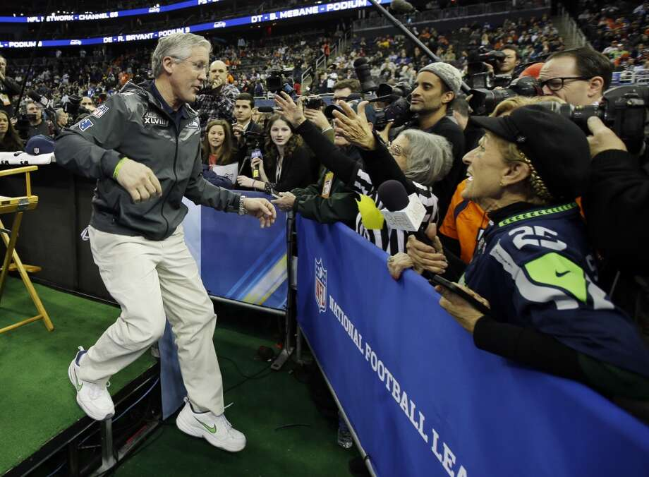 Seattle Seahawks head coach Pete Carroll goes to hug Teresa Dahlquist during media day for the NFL Super Bowl XLVIII football game Tuesday, Jan. 28, 2014, in Newark, N.J. (AP Photo/Matt Slocum) Photo: Matt Slocum, AP